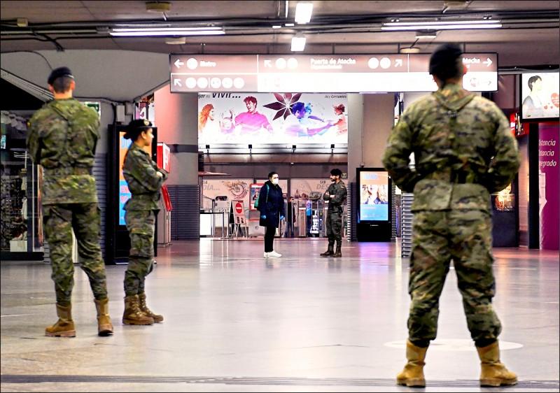 一名戴著口罩的婦女,十八日在西班牙首都馬德里最大的鐵路總站阿托查車站與駐守的軍人交談。(法新社)
