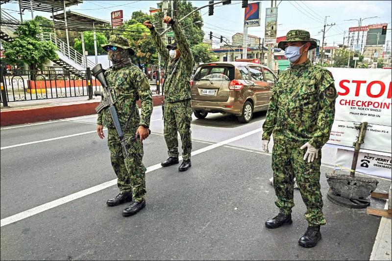 菲律賓防疫措施嚴峻,奎松市與首都馬尼拉市之間設有檢查哨,由戴上口罩的警方執勤。(法新社)