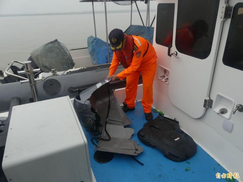 金門海巡人員檢視遭中船撞破的舷外機殼。(記者吳正庭攝)