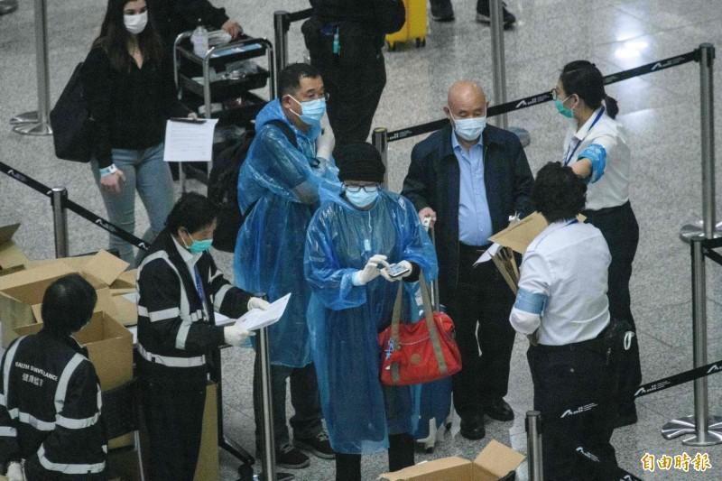 香港為防止新病病毒擴散已下令所有入境者強制居家隔離14天,圖為19日香港機場檢疫人員對入境旅客發放可追蹤行蹤的電子手環。(法新社)