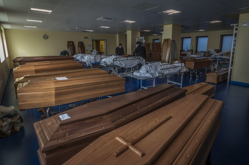 義大利當地重災區太平間的照片曝光,大量遺體等待移入木製棺材。(歐新社)