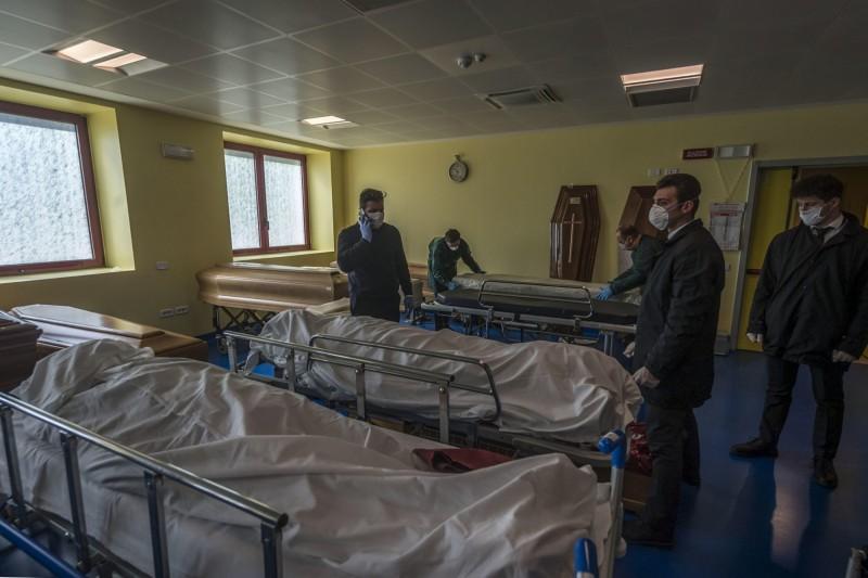 貝加莫城內的工人在太平間裡穿梭,無數的武漢肺炎死亡病患躺在擔架上,並用白布包裹遺體。(歐新社)