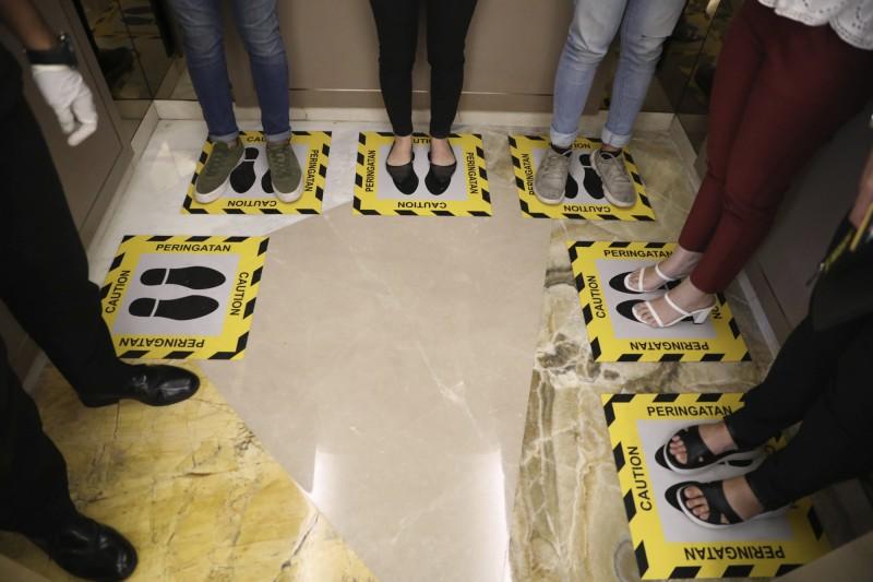 印尼泗水一間購物中心在電梯地板貼上標記,避免顧客站得太靠近而互相傳染。(美聯社)