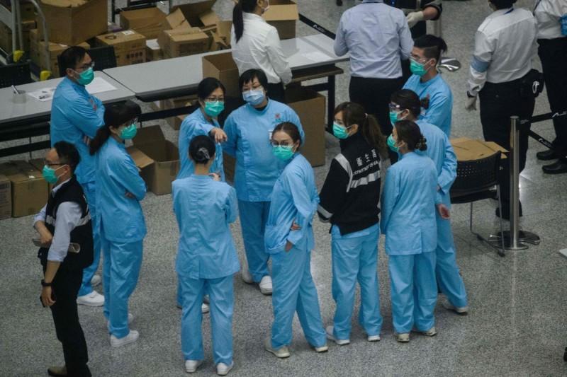香港今日再新增48例確診,再創單日新高,其中年齡最小的病患僅4歲,曾有英國旅遊史,目前無病徵。圖為香港檢疫人員。(法新社)