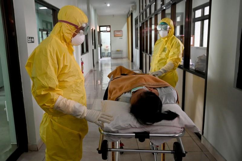 印尼峇里島桑拉醫院(Sanglah Hospital)中,身著防護衣的醫護人員,正將疑似武漢肺炎感染者送往檢測。(法新社)