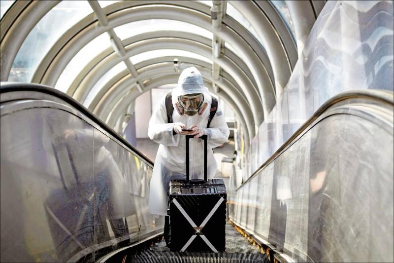 中國自稱當地「武漢肺炎」疫情趨緩,旅客廿一日卻依舊不敢大意,在首都北京車站全副武裝防疫。(路透)