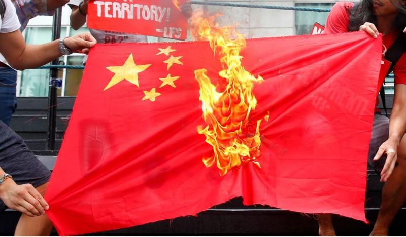 中國被外界認為趁著疫情積極進行「大外宣」美化形象。圖為燃燒的中國國旗。(美聯社檔案照)