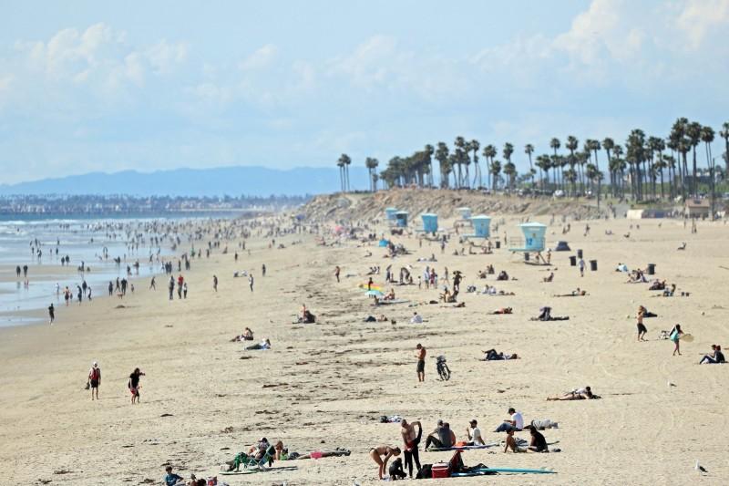 美國加州州長紐森(Gavin Newsom)呼籲民眾儘量待在家裡減少外出,但年輕人仍然到海灘開趴狂歡。圖為3月20日的加州海灘,依舊人山人海。(法新社)