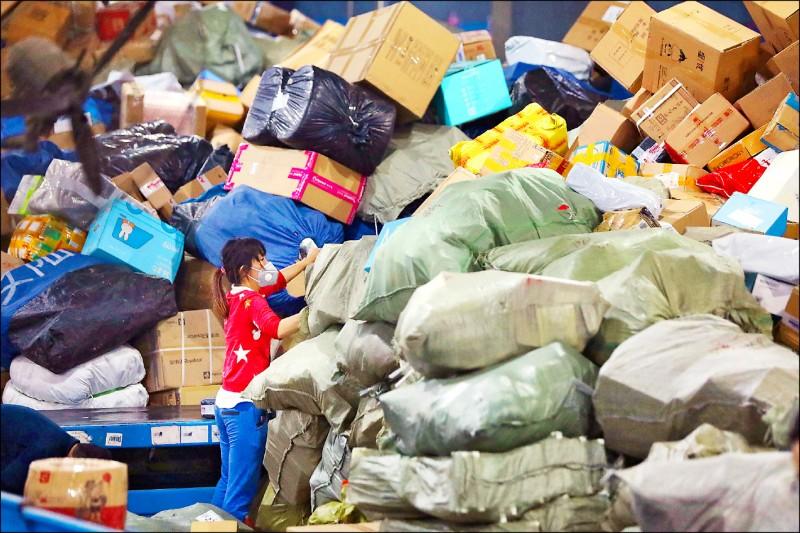 中國湖北省武漢市的中通快遞物流中心裡,一名員工在整理包裹。(路透)