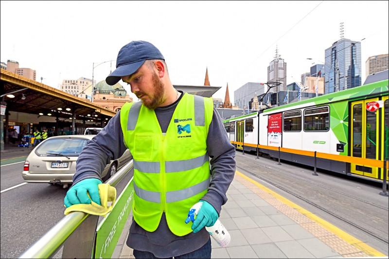 澳洲墨爾本的清潔人員廿五日仔細擦拭當地路面電車站周邊的欄杆。(歐新社)