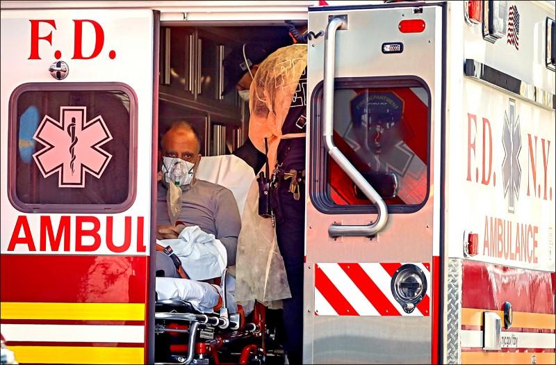 美國紐約市的緊急救護人員廿四日在救護車上協助固定一名武漢肺炎確診病患。美國的武肺死亡病例廿四日創單日新高,確診病例數仍以紐約州最多。(路透)
