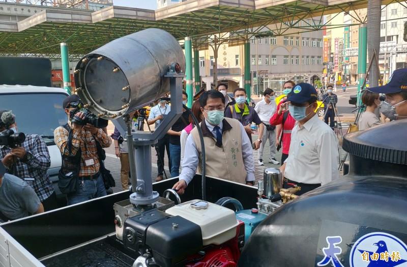 市長黃偉哲(中)對環保局自行研發的砲霧消毒車,給予高度肯定。(記者蔡文居攝)