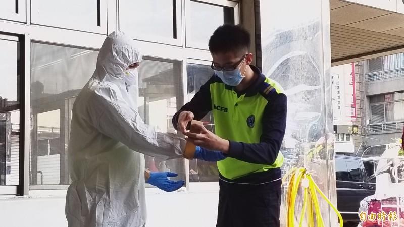 新竹縣消防人員現場示範演練穿著個人防護裝備,除了連身的防護衣,光是手套就要戴3層,並由他人協助每層用膠帶黏貼固定,以防脫落。(記者廖雪茹攝)