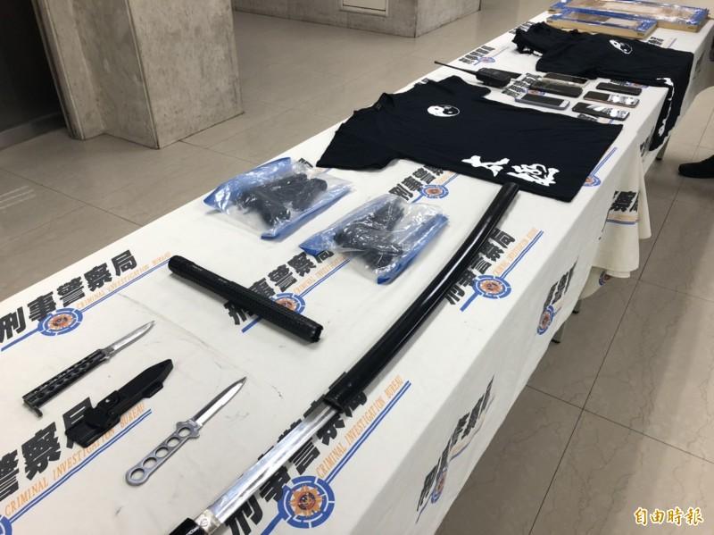 警方查扣電擊棒、幫派T恤、槍枝滑套、通槍條、安非他命吸食器、武士刀、匕首,以及改造手槍等贓證物。(記者邱俊福攝)
