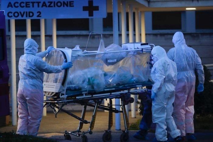 義大利醫療資源面臨崩潰,圖為羅馬的醫護人員移動確診病患。(美聯社)