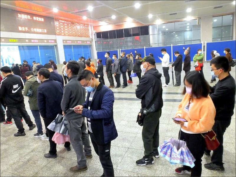 中國湖北省武漢市預定4月8日解除封城,但武漢有6成無症狀帶原者,恐引發第二波疫情大爆發!圖為湖北省宜昌解封,旅客大排長龍買火車票。(歐新社)