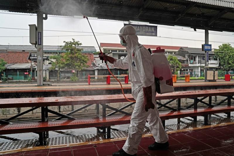 印尼今(26)日激增103例確診、20例死亡,累積總計893例確診,其中35人痊癒、78人死亡。首都雅加達亦廣設「消毒站」及「洗手站」,希望遏止疫情擴散。圖為印尼衛生人員進行消毒。(彭博)
