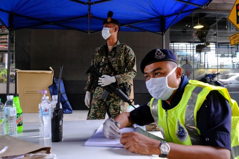 馬來西亞今(26)日更新病例數據,新增235例確診創下單日最高增幅,總確診數上升至2031例,其中23人死亡。圖為大馬軍警進行全國封鎖隔離。(彭博)