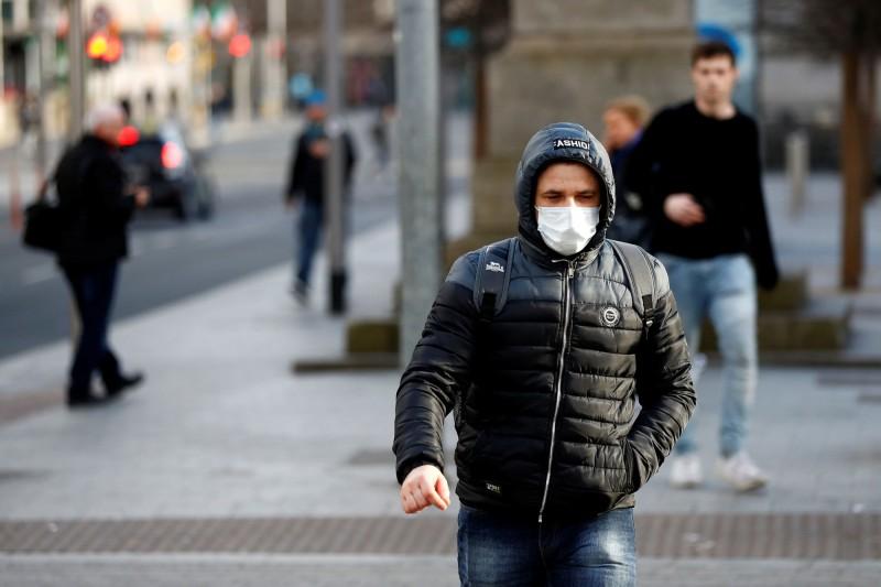 愛爾蘭昨(26日)武漢肺炎大爆發,共有10人死亡並新增255人確診。圖為都柏林行人戴上口罩外出。(路透)