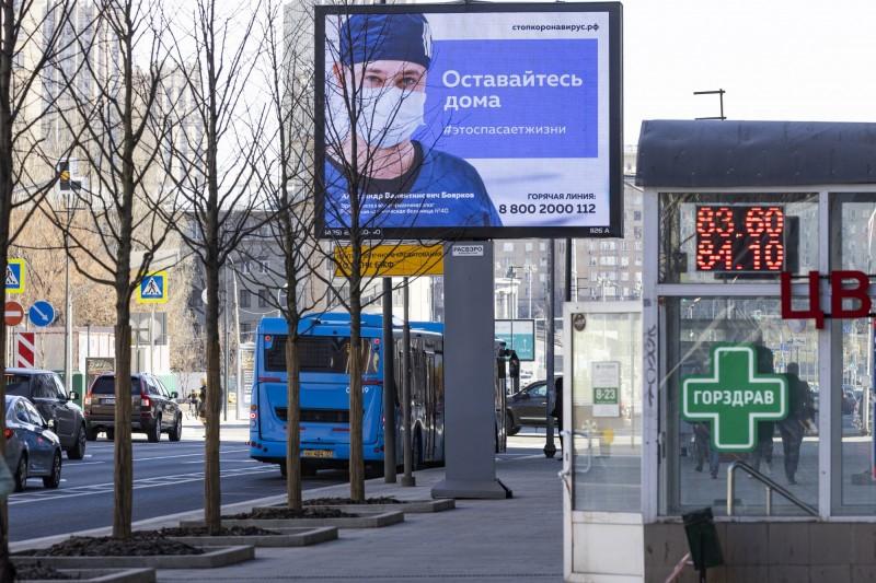 圖為俄羅斯莫斯科一條街道上,電子廣告看板畫面是醫生戴著口罩,寫著「待在家裡,將挽救一條生命」的標語。(美聯社)
