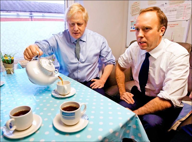 負責防疫重責的衛生大臣韓考克(右)同日也宣布確診。圖為他去年11月在保守黨的大選選戰活動中,與強森和選戰工作人員一起喝茶。(法新社)
