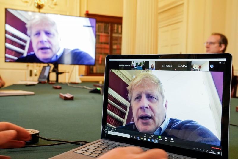 確診武漢肺炎的英國首相強森(Boris Johnson),將致信給3000萬個英國家庭,透露疫情「在變得更好之前會變得更糟」。圖為強森在自主隔離時透過視訊參加防疫會議。(歐新社)