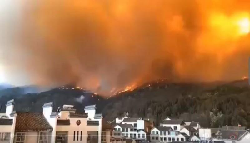 中國四川省西昌市旁馬鞍山、瀘山發生森林大火,城市天空佈滿濃煙與火光。(圖取自微博)