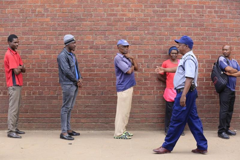 非洲辛巴威今起全國封閉21天試圖力阻武漢肺炎疫情擴散,一名警員正要求出門購買民生必需品的民眾遵守社交距離規定。(歐新社)