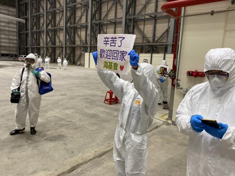 台飛維修棚廠臨時通關檢疫站內,海基會人員溫馨舉著「辛苦了!歡迎回家」的標語向搭機旅客致意。(讀者提供)