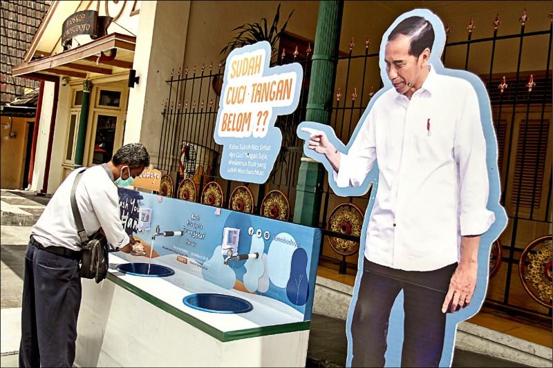 印尼政府正大力宣導勤洗手對抗武漢肺炎疫情的重要性。圖為爪哇島上的印尼文化藝術中心日惹(Yogyakarta),一名男子卅日戴著口罩在街上的洗手站認真洗手,一旁還有總統佐科威問道「洗過手了嗎?」的人形立牌。(路透)