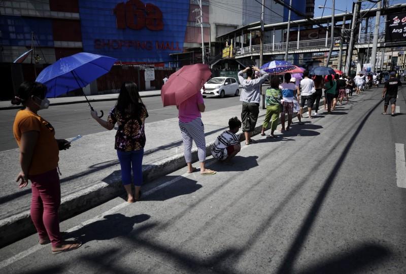 菲律賓衛生部今天通報新增29名武漢肺炎患者不治,單日新增死亡人數創疫情爆發以來最多,圖為菲律賓民眾在超市外保持距離排隊的情形。(歐新社)