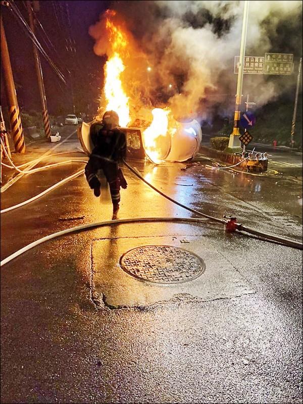 特斯拉自撞起火燃燒,消防人員趕赴現場灌救。(記者許倬勛翻攝)
