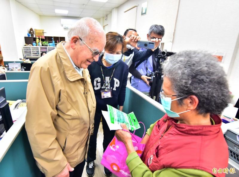 83歲何姓婦人,捐出自己辛苦排隊而來的口罩,以及1天賣菜所得,親手交給神父呂若瑟,「這是我的一點小心意。」(記者張議晨攝)