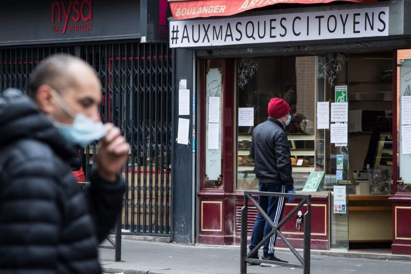 法國下令封城21天全民禁足試圖阻止武漢肺炎疫情繼續擴散,巴黎一家麵包店要求戴口罩才能入內。(法新社)
