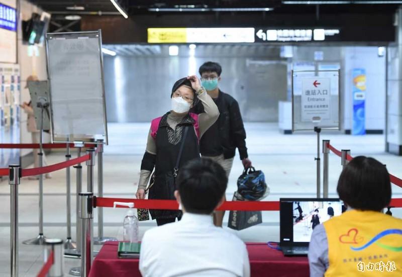 配合政府政策,大眾運輸系統站前量體溫,並要求民眾戴口罩進站。圖為台鐵站前量體溫。(記者方賓照攝)