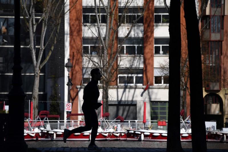 在4月1日法國全國封鎖令邁入第16天之際,一名男子在巴黎街上慢跑。(法新社)