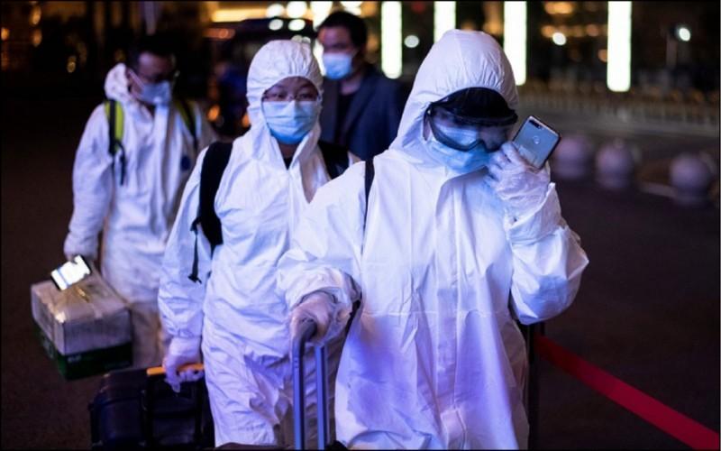武漢解封,民眾身穿防護服到武漢火車站搭車離開。(法新社)