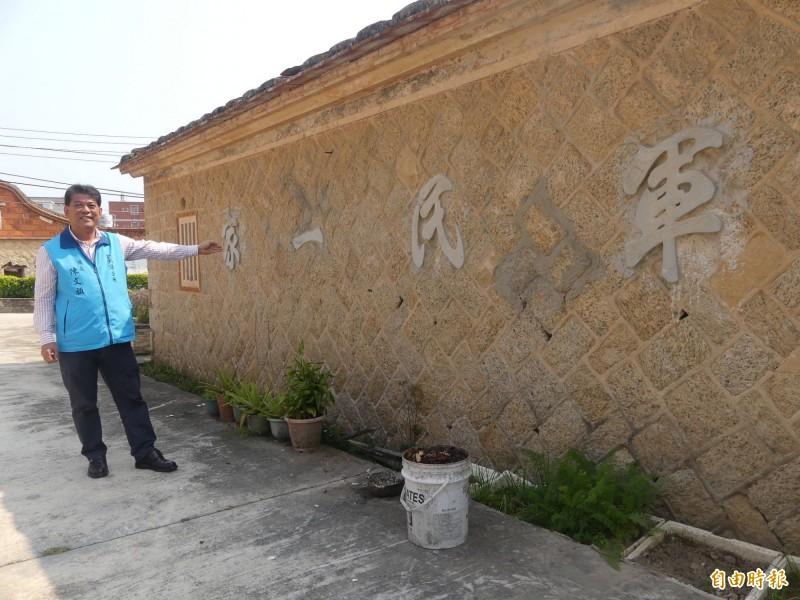 金湖鎮長陳文顧指著牆上「軍民一家」的標語說,這樣的房子早年幾乎都有軍隊駐紮在老百姓的家裡。(記者吳正庭攝)