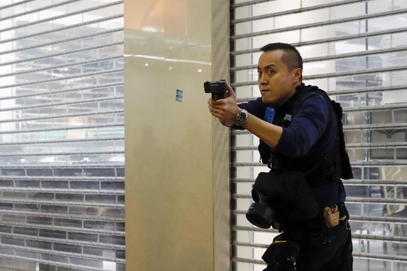 香港警察過去曾被譽為「亞洲最佳警察」,但在2019年爆發的「香港反送中運動」中,因暴力執法與黑警事件使香港警察跌落神壇,不僅警民關係迅速惡化,也使香港警察出現離職潮。圖為拔槍警告示威者的香港警察。(路透)