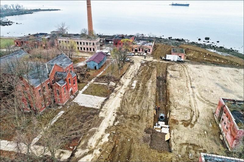 身著防護衣的工作人員9日在美國紐約市布朗區的哈特島上挖掘萬人塚,並將據信是死於武漢肺炎的死者棺木放入墓穴坑內。(美聯社)