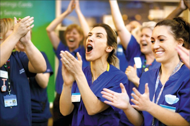 英國「國家醫療保健服務」(NHS)的工作人員九日在倫敦切爾西威斯敏斯特醫院外參加「為醫護鼓掌」活動,為在第一線對抗武漢肺炎的醫護人員加油打氣。這項活動由暫代首相職務的外相拉布在晚間八點揭開序幕,獲得全國各地民眾響應。(路透)