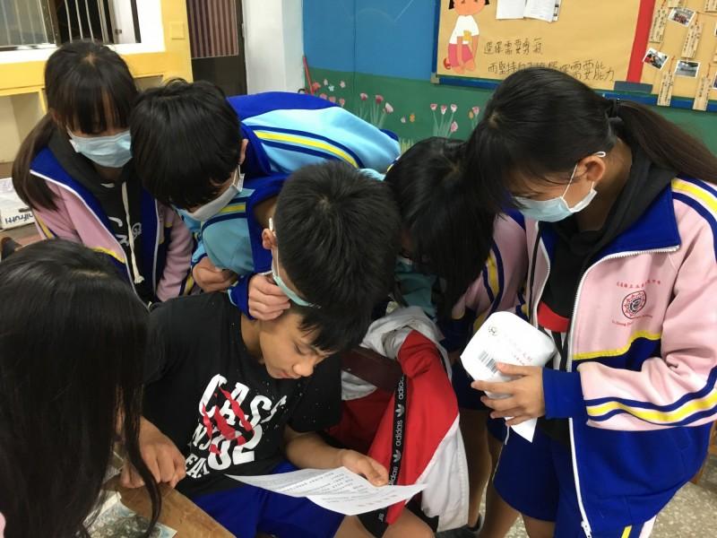 黃偉忠拿著總統府的回信閱讀,班上學生全都擠到他身邊要看,頓時成為全班焦點。(李慰萱提供)