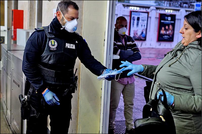 西班牙十三日恢復部分經濟活動,警方調派警力在馬德里郊區埃納雷斯堡(Alcala de Henares)車站發口罩給上班族。(歐新社)