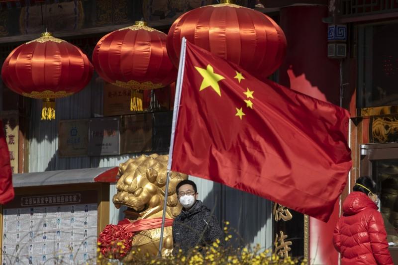 中國紅頭文件近日被揭漏,內容顯示中國1月3日前後就已開始部署疫情工作,但卻遲至1月20日才公開破除「可防可控」的謊言,近20天防疫關鍵期間強力隱匿疫情,恐怕即是造成病毒擴散全球的「人禍」。圖為中國民眾戴口罩站在國旗後方。(美聯社)