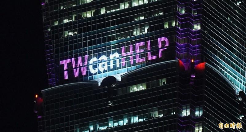 台北101大樓今晚在外牆亮起粉紅色的「TW can HELP」、「防疫不分你我」以及「台灣加油」等字樣,吸引路人駐足欣賞。(記者廖振輝攝)