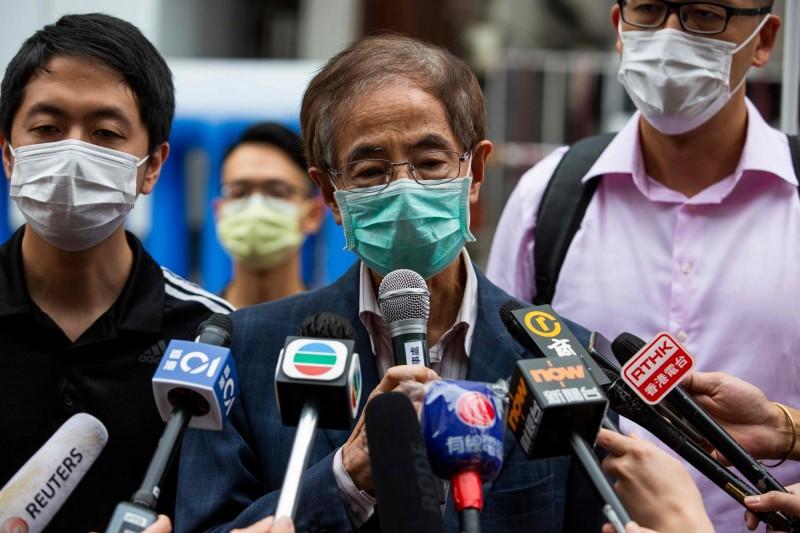 香港警方今天以涉嫌參加非法集結罪拘捕了泛民主派14名核心人士,民主黨創黨主席李柱銘(中)被捕獲准交保後說,這讓他有機會與一眾年輕人一起走民主路。(法新社)