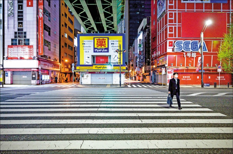 日本東京的知名商圈「秋葉原」,過去一向吸引許多想選購3C產品或喜愛電玩、動漫的逛街人潮。十七日街上卻空蕩蕩,只有一名戴口罩的上班族走過。(法新社)