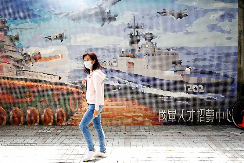 A woman walks past a Ministry of National Defense recruitment poster in Taipei yesterday. Photo: Ann Wang, Reuters