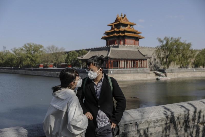 中國北京市朝陽區14日發生境外移入武漢肺炎病例,造成家人群聚感染,北京疾控中心已將朝陽區列為疫情高風險地區。圖為疫情下的北京紫禁城外,路人都戴著口罩。(歐新社)