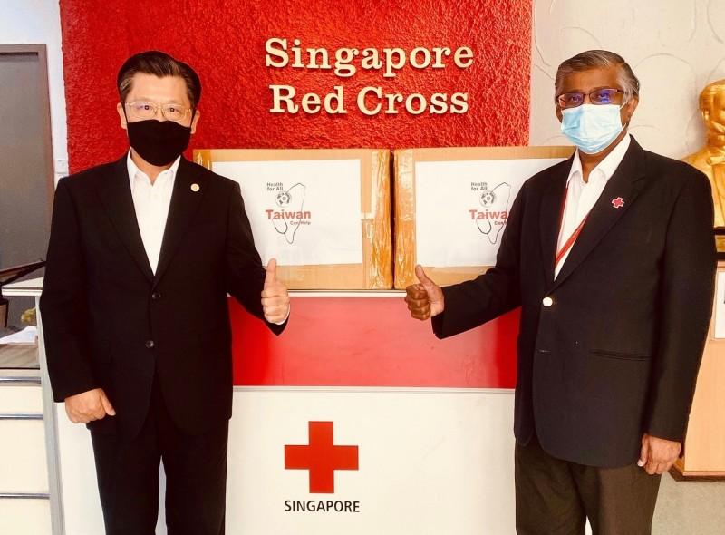 台灣捐贈星國的10萬片醫療口罩,今下午由駐星國代表梁國新(左)贈予新加坡紅十字會執行長兼秘書長Benjamin William。(取自駐新加坡台北代表處臉書)